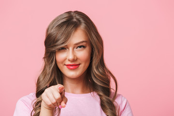 Hey you! Closeup photo of flirty lovely woman with long curly brown hair looking at camera and pointing finger, isolated over pink background