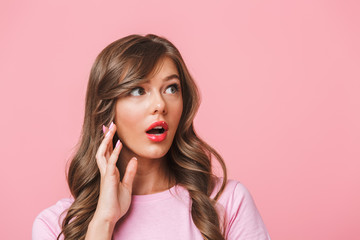 Photo closeup of excited pretty woman with long curly hair in basic t-shirt bulging eyes and looking aside with surprise and open mouth, isolated over pink background