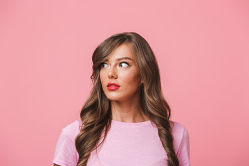 Photo closeup of surprised pretty woman with long curly hair expressing interest with open mouth and bulging eyes while looking aside at copyspace, isolated over pink background