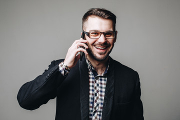 Young handsome business man in glasses, bearded in suit smiling and talking on mobile phone, cell phone isolated on grey background. Studio shot.
