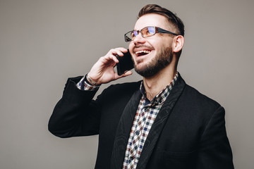 Side view shot of attractive brunette business man with glasses, in casual shirt, stylish black jacket talking on the cell phone and smiling. Isolated grey background. Studio