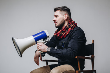 Young attractive movie director holding a megaphone. Film director talking on a loudspeaker while sitting on a chair isolated on grey background. Side view