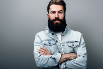 Brutal handsome fashionable young European male with thick beard wearing trendy denim jacket, cross hands, staring at camera with serious and cheerful look. Barber man posing against gray studio wall. Fotoväggar