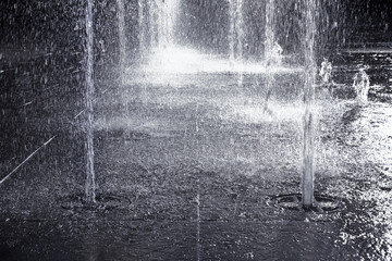 Water jets of a modern fountain on a stone pavement - toned image