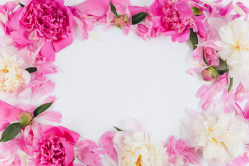 Floral frame wreath made of pink and white peonies flower buds. Flat lay, top view.