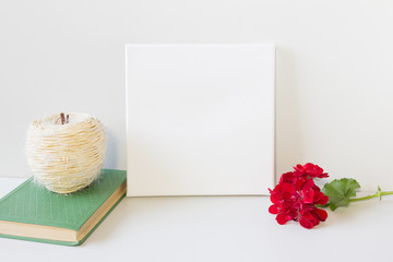 Mock-up poster and book with red flower. Blank canvas for image. Neutral gray interior on background.