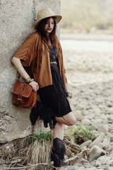 beautiful stylish boho woman with hat, leather bag, fringe poncho and boots. girl in gypsy hippie look young traveler posing near river rocks in mountains. sensual look. atmospheric moment.