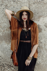stylish boho woman with jewelry posing at rock wall. beautiful hipster gypsy dressed girl with hat and fringe poncho with sensual look. young girl traveler. fashionable hippie outfit. summer vacation