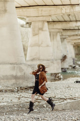 stylish boho woman jumping, having fun, in hat, leather bag, fringe poncho and boots  near river under bridge stone. girl in gypsy hippie look young traveler. summer travel