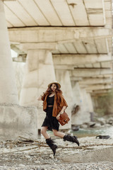 stylish boho woman jumping, having fun, in hat, leather bag, fringe poncho and boots  near river under bridge stone. girl in gypsy hippie look young traveler. joyful moments.