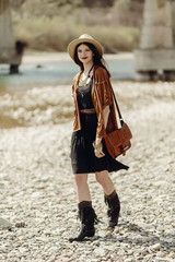 stylish hipster woman in hat, fringe poncho and boots walking on river beach. boho traveler girl in gypsy look, summer travel. atmospheric moment.  space for text.
