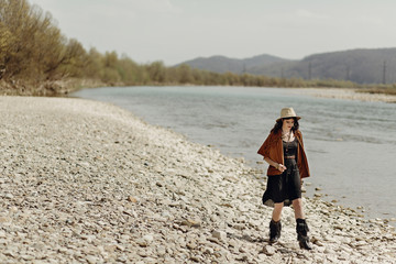 stylish boho traveler woman in hat, fringe poncho and boots walking on river beach, boho hipster girl look, summer travel. atmospheric moment. space for text.