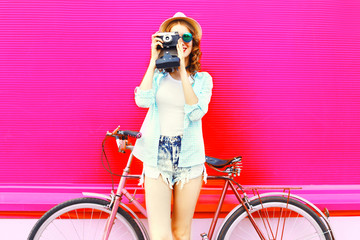 Fuuny girl with retro camera and bicycle over colorful pink background