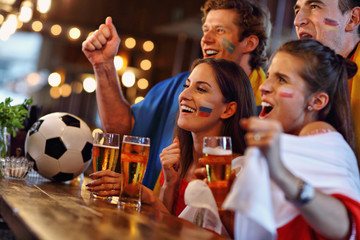 Group of friends watching soccer in pub