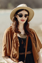 stylish hipster boho woman in sunglasses with hat, leather bag, fringe poncho and accessory. traveler girl look, near beach in mountains. atmospheric moment. summer travel.