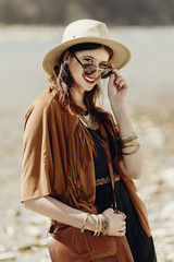 stylish hipster boho woman smiling in sunglasses with hat, leather bag, fringe poncho and accessory. traveler girl look, near beach in mountains. atmospheric moment. summer travel.