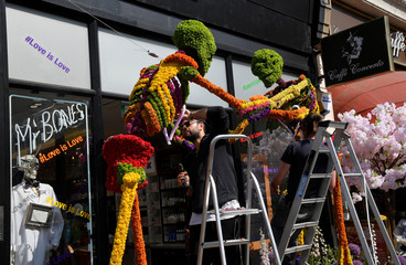 Florists work on a floral display and design outside of a shop front which is participating in the Chelsea In Bloom festival in London, Britain