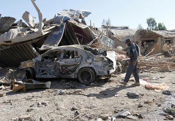 An Afghan policeman inspects a damaged vehicle at the site of a blast in Kandahar province, Afghanistan