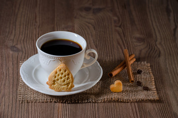 a cup of coffee and cookies like strawberry and heart with cinnamon, coffee beans on wooden table