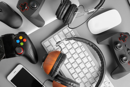 Gamepads, mice, headphones and keyboard on table
