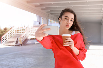 Attractive young woman taking selfie with phone outdoors