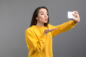 Attractive young woman taking selfie with phone on color background