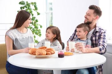 Happy family having breakfast with milk at table