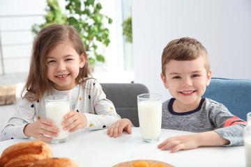 Cute little kids having breakfast with milk at table