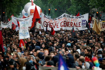 French civil servants and students carry labour union flags as they march in protest during a national day of strikes by public sector workers, in Paris