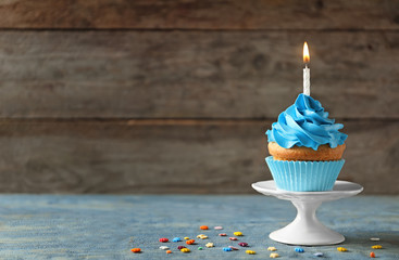 Delicious birthday cupcake with candle on table