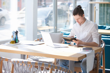 Charming and thoughtful man, an outsourcing employee of large business center, opens his laptop sitting at table in cafe next to notebook and phone