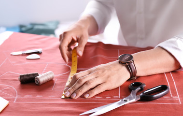 Tailor working at table in atelier, closeup