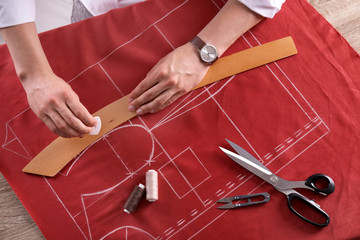 Tailor working at table in atelier, top view