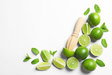 Flat lay composition with lime, mint and juicer on light background. Refreshing beverage ingredients