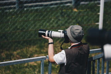 professional photographer with camera and telephoto lens in the filed taking photo of sports events