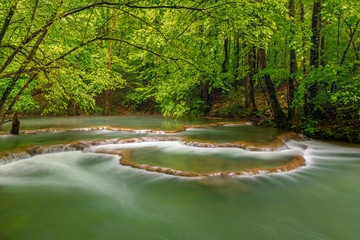 French landscape - Jura. River with small waterfalls in the Jura mountains after rain.