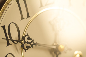 Face of classical grandfather pendulum clock closeup in golden light in concept of golden hour.