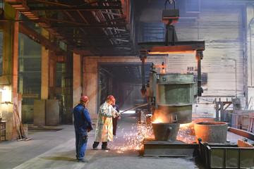 Gruppe Arbeiter in einer Giesserei - Herstellung von Gussteilen in einer Fabrik // Group of workers in a foundry - Production of castings in a factory