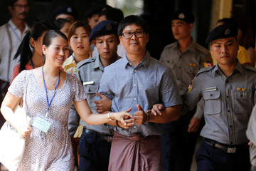Detained Reuters journalist Wa Lone is escorted by police before a court hearing in Yangon