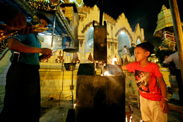 A boy lights a candle in Kaba Aye Pagoda during Myanmar's new year, in Yangon