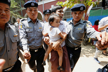 Detained Reuters journalist Kyaw Soe Oo carries his daughter Moe Thin Wai Zin during a break at the court hearing in Yangon