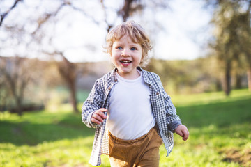 Happy toddler boy running outside in spring nature.
