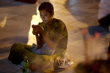 A woman looks at her phone as she sits in Kaba Aye Pagoda during Myanmar's new year, in Yangon