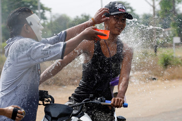 A man splashes a motorbike driver with water during Thingyan festival celebrations to commemorate the Burmese New Year in Pyay