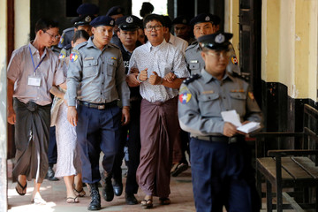 Detained Reuters journalist Wa Lone is escorted by police before a court hearing in Yangon Myanmar