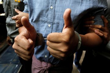 Detained Reuters journalist Wa Lone gives a thumbs up as he is escorted by police after a court hearing in Yangon