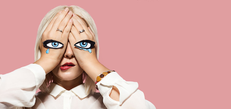 Sad woman crying. Girl closed eyes, eyes and tears painted on her hands. Portrait of fashionable young model. Emotion of sadness and sorrow. Pink wall on background.
