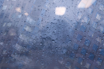 Rainy day background with rain drop on to window office building.