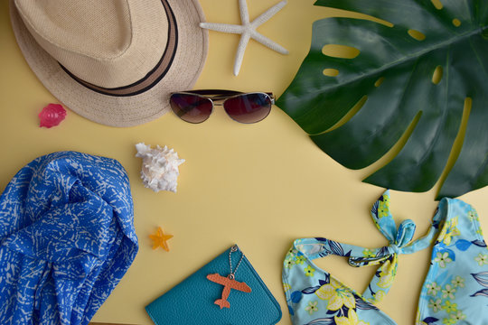 Woman's accessories for summer travel flay lay on bright yellow background with colorful bikini, sun glasses, a hat, passport holder and sea shells (copy space for text)