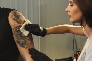 Woman tattoist wiping finished tattoo with napkin